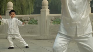 MS Young boy following Tai Chi moves after mature man in foreground in a park/ Beijing, China