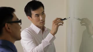 MS Young business man writing on white board, talking to colleague in office / China