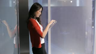 MS Young business woman using digital tablet leaning on glass wall / China