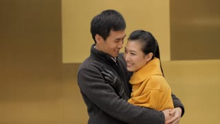 MS Young couple hugging and smiling against yellow wall / China