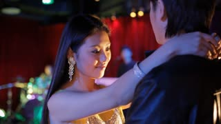 MS Young couple smiling and slow dancing in night club / China