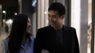 MS Young couple walking and talking on street at night / China