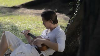 MS Young man playing ukulele under tree