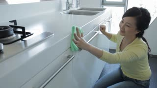 MS Young woman cleaning kitchen counter cabinets / China