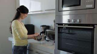 MS Young woman preparing food in her kitchen / China