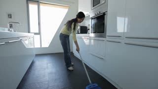 MS Young woman sweeping kitchen floor / China