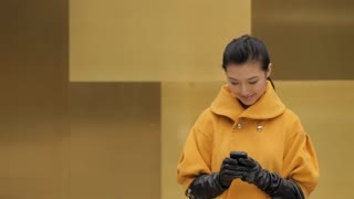MS Young woman wearing yellow coat using mobile phone and smiling