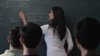 MS Young woman writing mathematical formula on blackboard in classroom