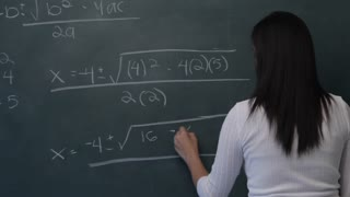 MS Young woman writing mathematical formula on blackboard, then smiling at camera
