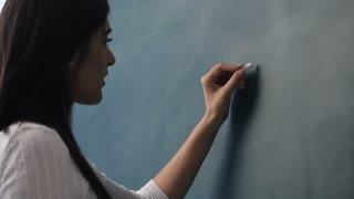 MS Young woman writing mathematical formula on blackboard
