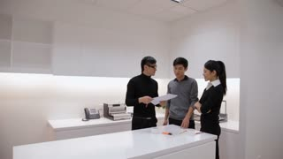MS ZI Portrait of business men and woman standing with paperwork by table in office / China
