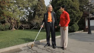 MSD TD Elderly couple writing Chinese calligraphy with water on pavement in park/ Beijing, China