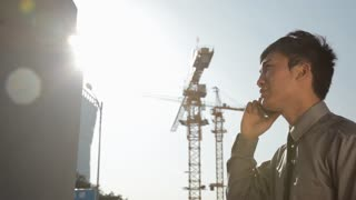 PAN MS LA Businessman talking on the mobile phone with cranes in background / Beijing, China