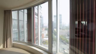 PAN MS Young man looking at the view through apartment window / China