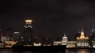 PAN WS Container ship moving along Huangpu River and The Bund skyline at night / Shanghai, China