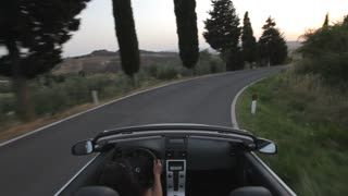 POV of car driving down winding road, Tuscany, Italy