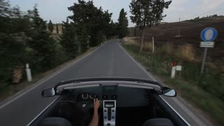 POV of car driving down winding road/ Tuscany, Italy