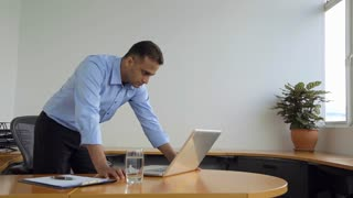 SELECTIVE FOCUS Businessman leans on desk looking at his laptop / Singapore
