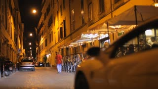 Sports car driving by street cafe at night / Rome, Italy