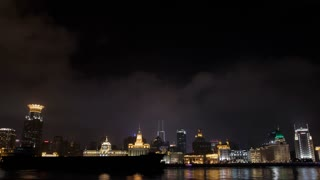 T/L WS Huangpu River with ships passing by and city lights going off on The Bund at night / Shanghai, China