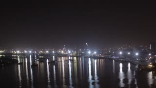 T/L WS LD Boats and Cranes Moving Along Saigon River at Night / Ho Chi Minh, Vietnam