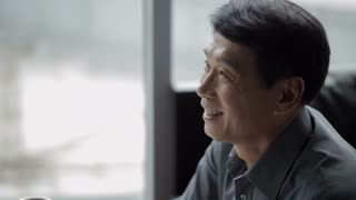 TD CU Mature businessman smiling and working in front of window / China
