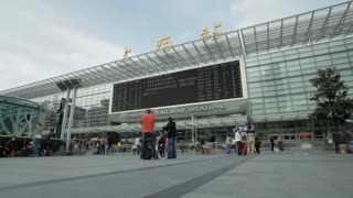 TL WS Shanghai Railway Station with big screen and people walking in foreground / Shanghai, China