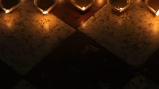 TU MS HA Burning clay oil lamps on tiled floor / Singapore