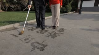 TU MS Mature couple writing Chinese calligraphy with water on pavement in park / Beijing, China