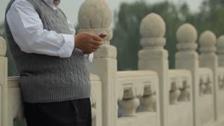 TU MS Mature man talking on mobile phone leaning on stone balustrade / China
