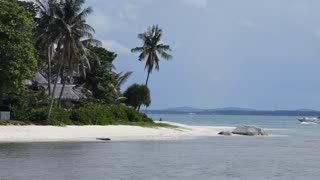 WS Boat sailing past island with villas / Indonesia