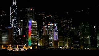 WS Boats floating by city skyline at night / Hong Kong