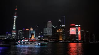WS Boats floating past city skyline at night / Shanghai, China