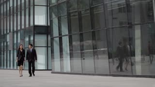 WS Businessman and businesswoman walking away from office building / Beijing, China