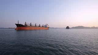 WS Container ship at dusk in bay / Ha Long Bay, Vietnam