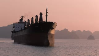 WS Container ship in bay at sunset / Ha Long Bay, Vietnam