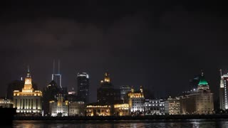 WS Container ship moving past The Bund skyline at night / Shanghai, China