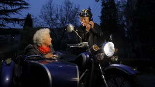 WS Elderly couple getting ready to ride a motorcycle with sidecar at night / China