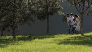 WS Family with two children walking through park towards camera / China
