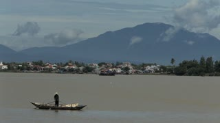 WS Fisherman Rowing Boat in Water with Mountain in Background / Hoi An, Vietnam