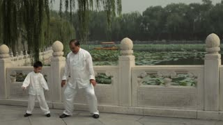 WS Grandfather and grandson doing Tai Chi in a park by lake /Beijing, China