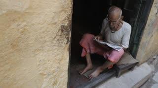 WS HA Man sitting in doorway reading newspaper / Varanasi, India