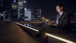 WS LD Businessman Sitting on Bench Working on Laptop with City Scape in Background at Night / Singapore
