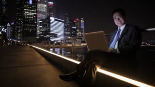 WS LD Businessman Sitting Outside Working on Laptop with Illuminated Buildings in Background at Night / Singapore