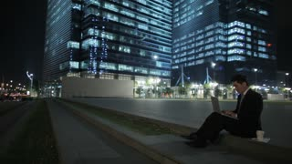 WS LD Young Businessman Sitting on Steps in front of Buildings, Working on Laptop at Night / Singapore