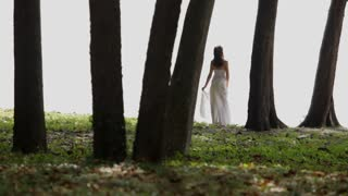 WS LS Woman in long white dress standing in forest / Singapore