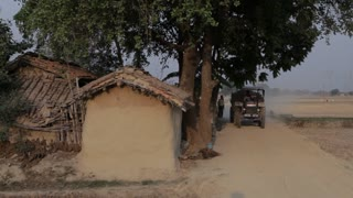 WS Man Driving Tractor down Dirt Road in Village / Saranth, India