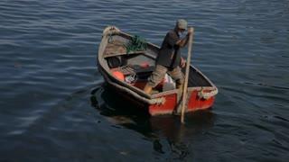 WS Man Rowing Boat in Water / Cornwall, England, UK