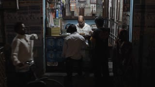 WS Man selling things in small shop at night / India