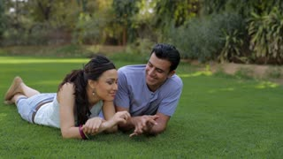 WS Mid-adult couple lying on grass, talking / India